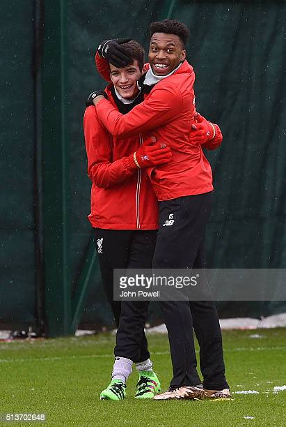 Daniel Sturridge embraces Pedro Chirivella of Liverpool during a training session at Melwood Training Ground on March 4 2016 in Liverpool England