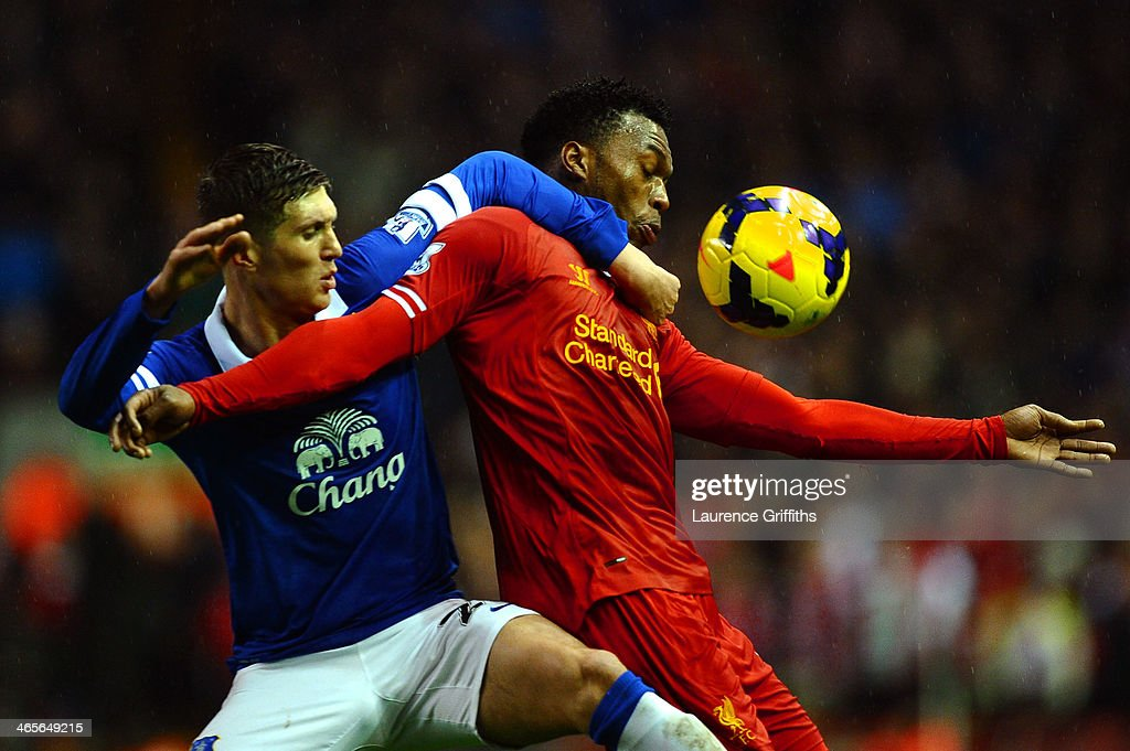 Daniel Sturridge of Liverpool attempts to control the ball under pressure from John Stones of Everton during the Barclays Premier League match between Liverpool and Everton at Anfield on January 28, 2014 in Liverpool, England.