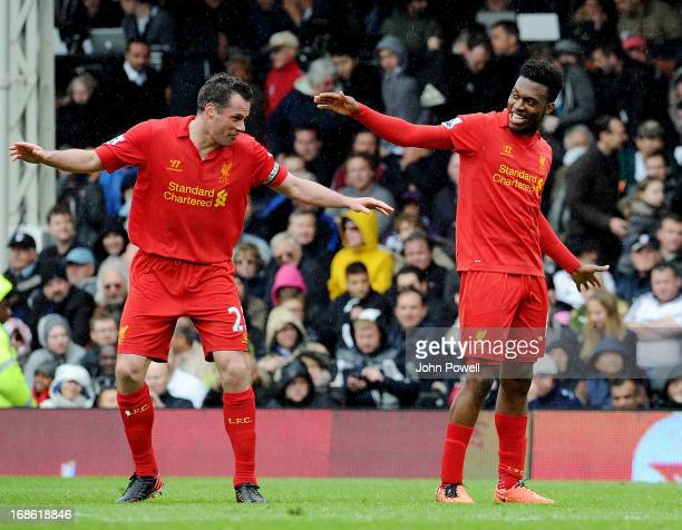 Daniel Sturridge of Liverpool celebrates after his hat-trick goal with Jamie Carragher during the Barclays Premier League Match between Fulham and...