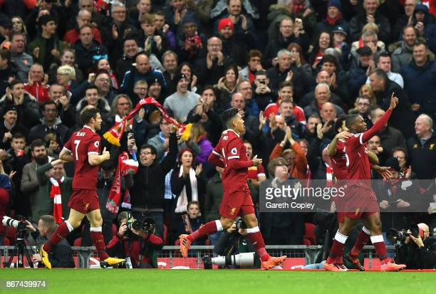 Daniel Sturridge of Liverpool celebrates scoring his sides first goal with his Liverpool team mates during the Premier League match between Liverpool...