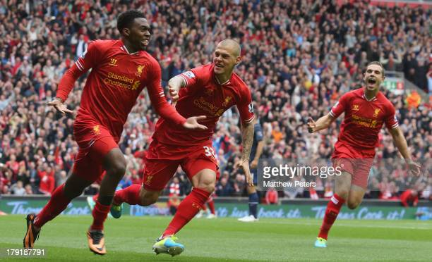 Daniel Sturridge of Liverpool celebrates scoring their first goal with Martin Skrtel during the Barclays Premier League match between Liverpool and...