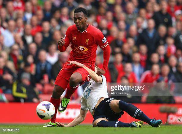 Daniel Sturridge of Liverpool is challenged by Michael Dawson of Tottenham Hotspur during the Barclays Premier League match between Liverpool and...