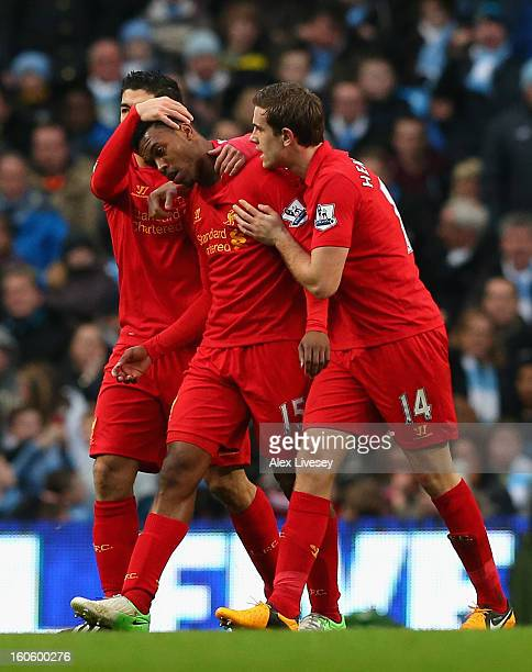 Daniel Sturridge of Liverpool is congratulated by his teammates Luis Suarez and Jordan Henderson after scoring his team's first goal during the...