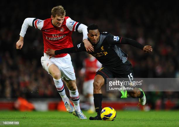 Daniel Sturridge of Liverpool loses his boot as he battle for the ball with Per Mertesacker of Arsenal during the Barclays Premier League match...