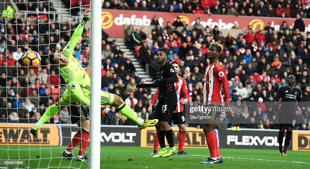 Daniel Sturridge of Liverpool (C) scores his sides first goal past Vito Mannone of Sunderland (L) during the Premier League match between Sunderland and Liverpool at Stadium of Light on January 2, 2017 in Sunderland, England.