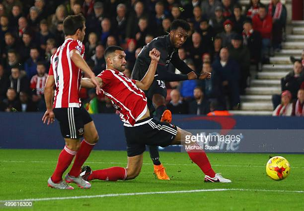 Daniel Sturridge of Liverpool shoots past Steven Caulker of Southampton to score their first goal during the Capital One Cup quarter final match...