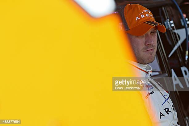 Daniel Suarez driver of the ARRIS Toyota looks on in the garage area during practice for the NASCAR Camping World Truck Series NextEra Energy...