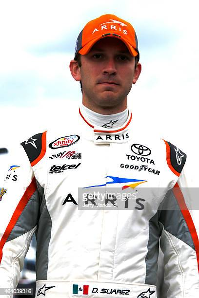Daniel Suarez driver of the ARRIS Toyota walks on the grid during qualifying for the NASCAR XFINITY Series Alert Today Florida 300 at Daytona...