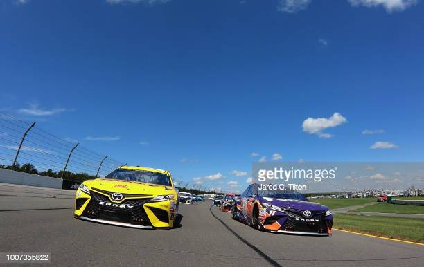 Daniel Suarez driver of the Stanley Toyota and Denny Hamlin driver of the FedEx Express Toyota lead the field prior to the start of the Monster...