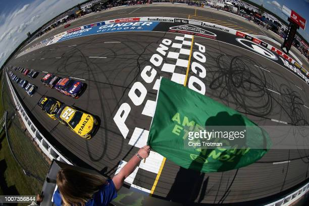 Daniel Suarez, driver of the Stanley Toyota, and Denny Hamlin, driver of the FedEx Express Toyota, lead the field to the green flag to start the...