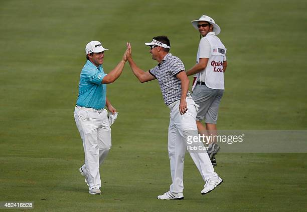 Daniel Summerhays celebrates a eagle in the 14th fairway with Robert Allenby of Australia during the first round of the Quicken Loans National at the...