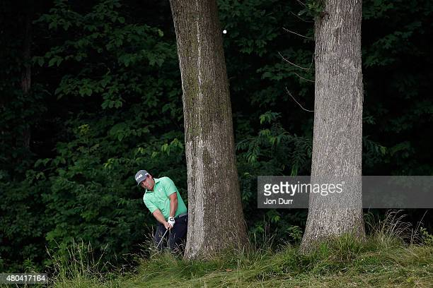 Daniel Summerhays takes a shot in the rough behind a tree on the first hole during the third round of the John Deere Classic held at TPC Deere Run on...