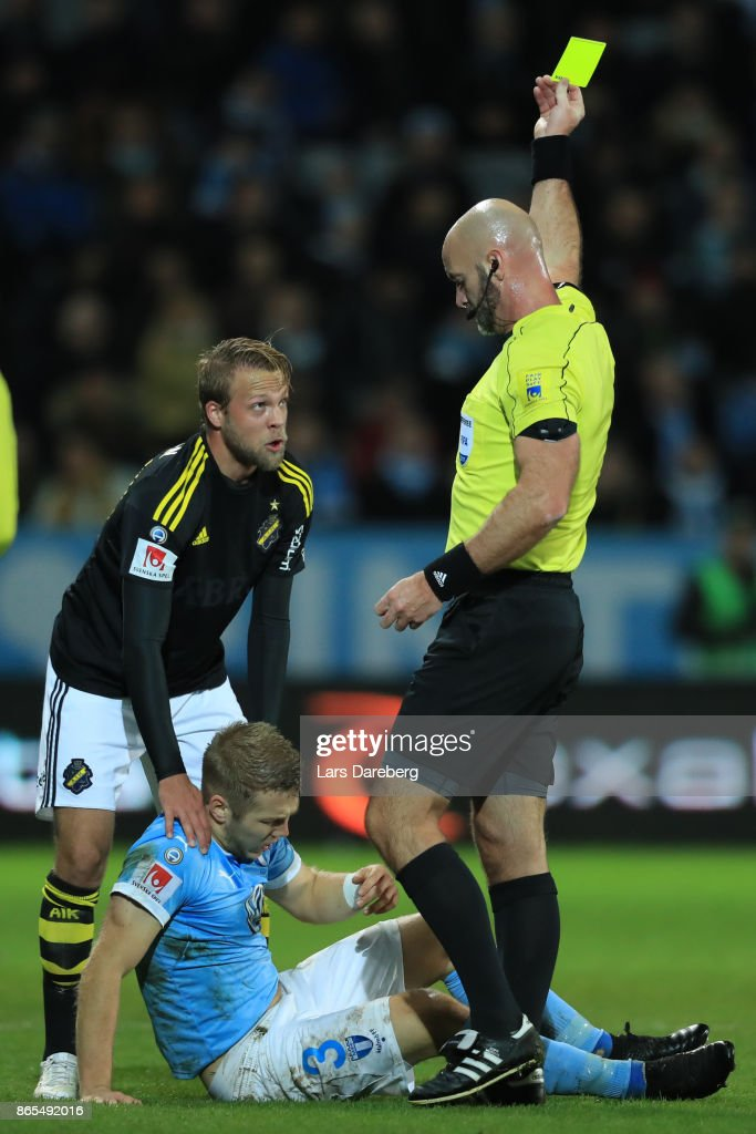 Daniel Sundgren get a yellow card from referee Stefan Johanessen and Anton Tinnerholm of Malmo FF during the allsvenskan match between Malmo FF and AIK at Swedbank Stadion on October 23, 2017 in Malmo, Sweden.