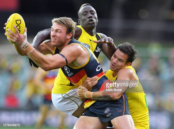 Daniel Tahlia of the Crows tackled by Daniel Rioli of the Tigers and Mabior Chol of the Tigers during the round 18 AFL match between the Adelaide...