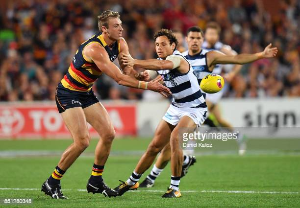 Daniel Talia of the Crows handballs as Steven Motlop of the Cats defends during the First AFL Preliminary Final match between the Adelaide Crows and...