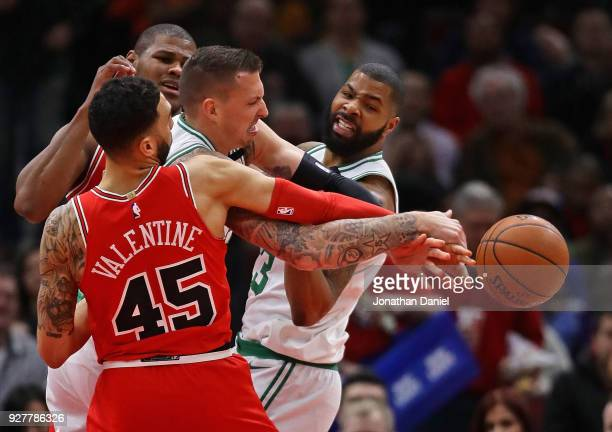 Daniel Theis of the Boston Celtics battles for the ball with Denzel Valentine and Cristiano Felicio of the Chicago Bulls at the United Center on...