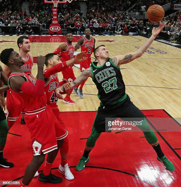 Daniel Theis of the Boston Celtics grabs a rebound next to Bobby Portis and Denzel Valentine of the Chicago Bulls at the United Center on December 11...
