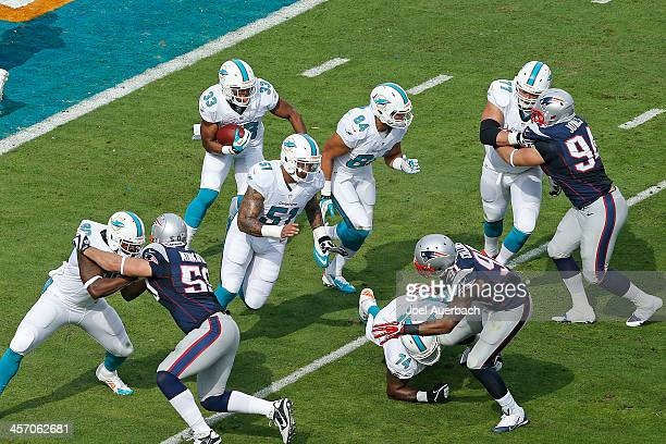 Daniel Thomas follows the blocks of Mike Pouncey and Michael Egnew of the Miami Dolphins as he runs with the ball against the New England Patriots on...