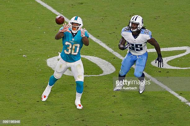 Daniel Thomas of the Miami Dolphins catches the ball in front of Sean Spence of the Tennessee Titans during a preseason game on September 1 2016 at...