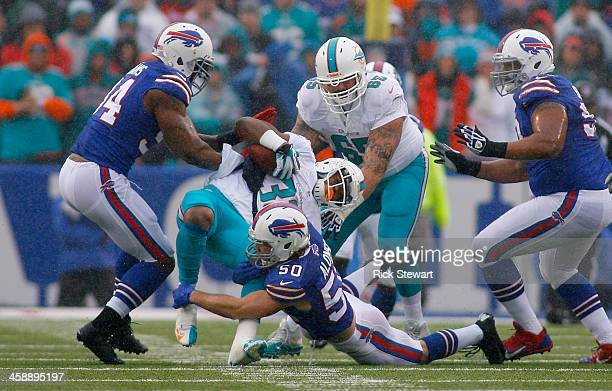 Daniel Thomas of the Miami Dolphins is tackled by Kiko Alonso of the Buffalo Bills at Ralph Wilson Stadium on December 22, 2013 in Orchard Park, New...