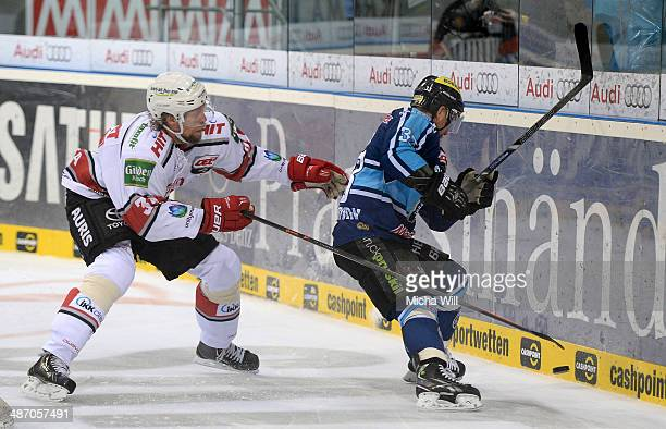 Daniel Tjaernqvist of Koeln and Bjoern Barta of Ingolstadt battle for the puck in game six of the DEL final playoffs between ERC Ingolstadt and...
