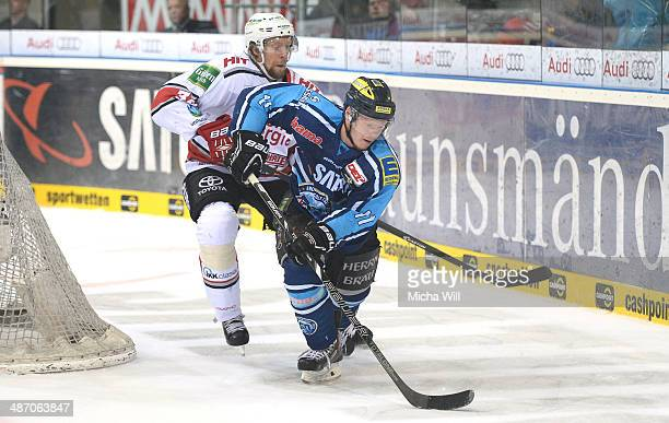 Daniel Tjaernqvist of Koeln and Christoph Gawlik of Ingolstadt battle for the puck in game six of the DEL final playoffs between ERC Ingolstadt and...