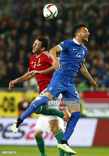 Daniel Tozser of Hungary and Andreas Samaris of Greece vie for the ball during their Euro 2016 qualification soccer match at Grupama Arena in...