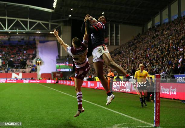 Daniel Tupou of Sydney Roosters claims the high ball against Tom Davies of Wigan Warriors to score their fourth try during the World Club Challenge...