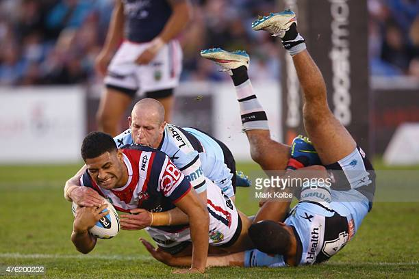 Daniel Tupou of the Roosters is tackled by Jeff Robson and Jayson Bukuya of the Sharks during the round 13 NRL match between the Sharks and the...