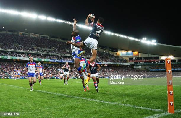 Daniel Tupou of the Roosters jumps high to beat Akuila Uate of the Knights to score a try during the NRL Preliminary Final match between the Sydney...