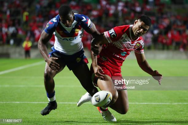 Daniel Tupou of Tonga competes with a loose ball with Jermaine McGillvary of Great Britain during the International Rugby League Test match between...
