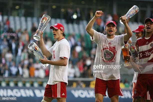 Daniel van Buyten and Mark van Bommel with beer celebrating after the Bundesliga match VfL Wolfsburg vs. Bayern Munich in Wolfsburg, Germany. Munich...