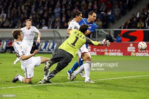 Daniel van Buyten of Muenchen scores his team's second goal against goalkeeper Daniel Haas and Josip Simunic of Hoffenheim during the Bundesliga...