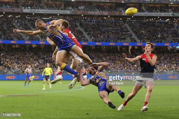 Daniel Venables of the Eagles collides with Nathan Vardy and Tim Smith of the Demons in a marking contest during the round nine AFL match between the...