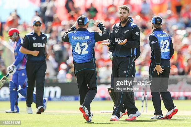 Daniel Vettori of New Zealand is congratulated by teammate Brendon McCullum after taking the wicket of Usman Ghani of Afghanistan during the 2015 ICC...
