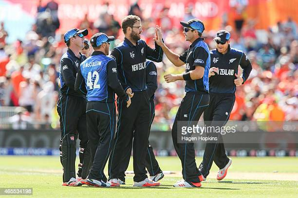 Daniel Vettori of New Zealand is congratulated by teammate Tim Southee after taking the wicket of Usman Ghani of Afghanistan during the 2015 ICC...