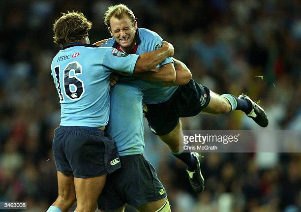 Daniel Vickerman of the Waratahs and Adam Freier pick up team mate Chris Whitaker as they celebrate their victory over the Brumbies during the Super...