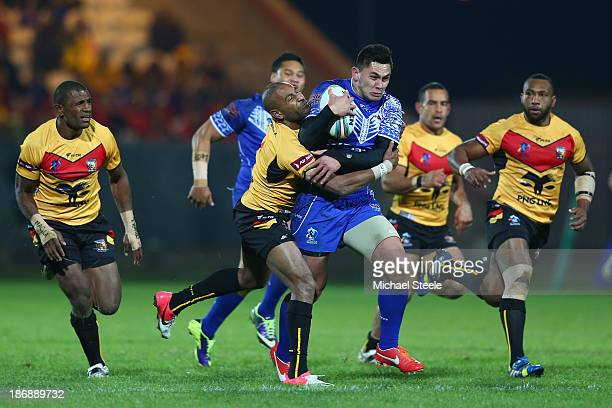 Daniel Vidot of Samoa is held up by Josiah Abavu of Papua New Guinea during the Rugby League World Cup Group B match between Papua New Guinea and...