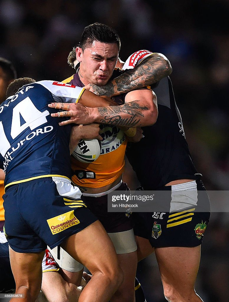 Daniel Vidot of the Broncos is tackled by Ray Thompson and Tariq Sims of the Cowboys during the NRL 1st Elimination Final match between the North Queensland Cowboys and the Brisbane Broncos at 1300SMILES Stadium on September 13, 2014 in Townsville, Australia.