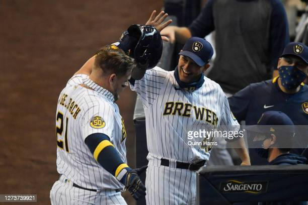 Daniel Vogelbach of the Milwaukee Brewers celebrates with hitting coach Andy Haines of the Milwaukee Brewers after his two run home run in the first...