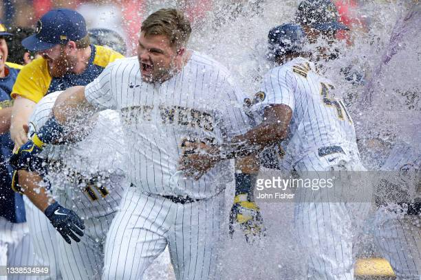Daniel Vogelbach of the Milwaukee Brewers gets a water and gatorade bath after hitting a walk-off grand slam in the ninth inning against the St....