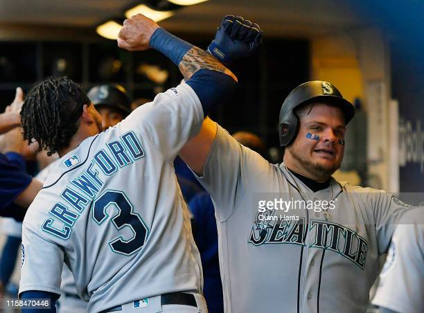 Daniel Vogelbach of the Seattle Mariners celebrates in the dugout with JP Crawford of the Seattle Mariners after hitting a two run home run in the...
