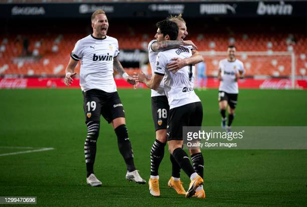 Daniel Wass of Valencia CF celebrates after scoring his team's first goal with his teammate Goncalo Guedes during the La Liga Santander match between...