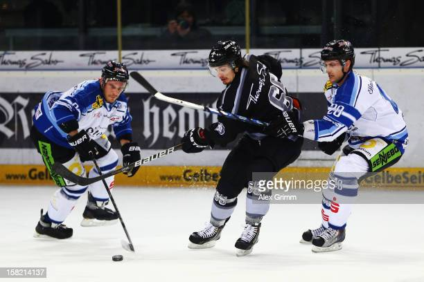 Daniel Weiss of Ice Tigers is challenged by Sebastian Osterloh and Matt Hussey of Straubing during the DEL match between Thomas Sabo Ice Tigers and...