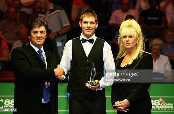 Daniel Wells is presented with the Paul Hunter Scholarship Trophy by Hunter's parents Alan and Christine during the 888com World Championship at the...