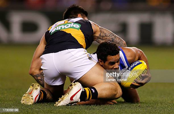 Daniel Wells of the Kangaroos is tackled by Aaron Edwards of the Tigers during the round 15 AFL match between the North Melbourne Kangaroos and the...