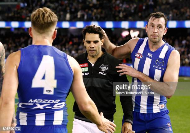 Daniel Wells of the Magpies chats with former Kangaroos teammates Shaun Higgins and Todd Goldstein during the 2017 AFL round 20 match between the...