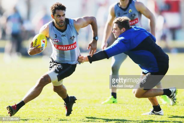 Daniel Wells runs with the ball away from Ben Kennedy during a Collingwood Magpies AFL training at the Holden Centre on July 11 2017 in Melbourne...