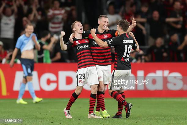 Daniel Wilmering Pirmin Schwegler and Mitchell Duke of the Wanderers celebrate victory during the round three ALeague match between the Western...