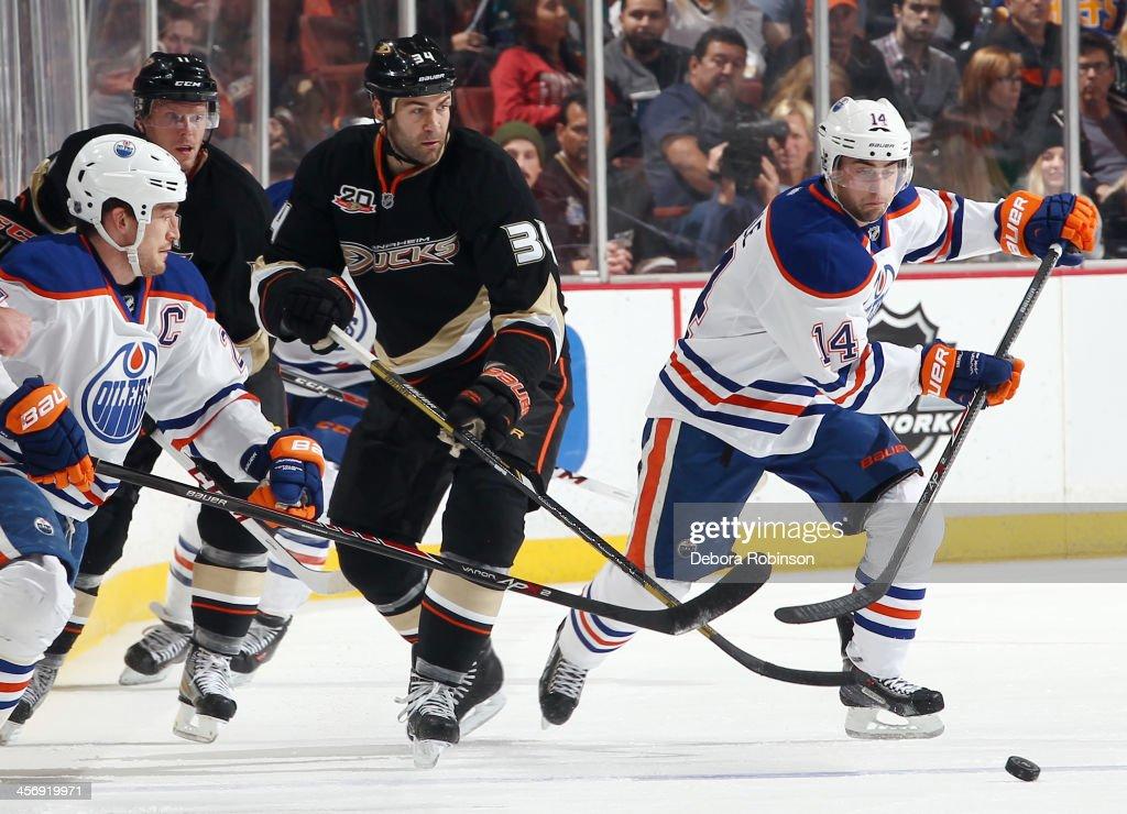 Daniel Winnik #34 of the Anaheim Ducks battles for the puck against Jordan Eberle #14 of the Edmonton Oilers on December 15, 2013 at Honda Center in Anaheim, California.